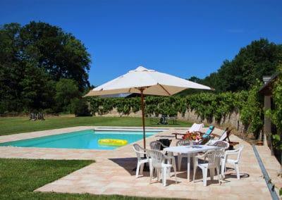 Vue sur la piscine de l'Orangerie entourée de son vaste jardin arboré